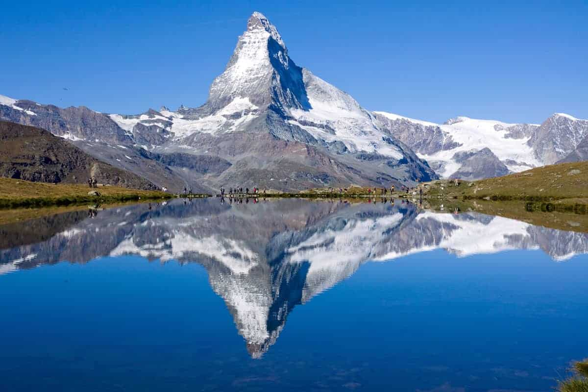Matterhorn perfectly reflected in the lake with tourists standing in front.