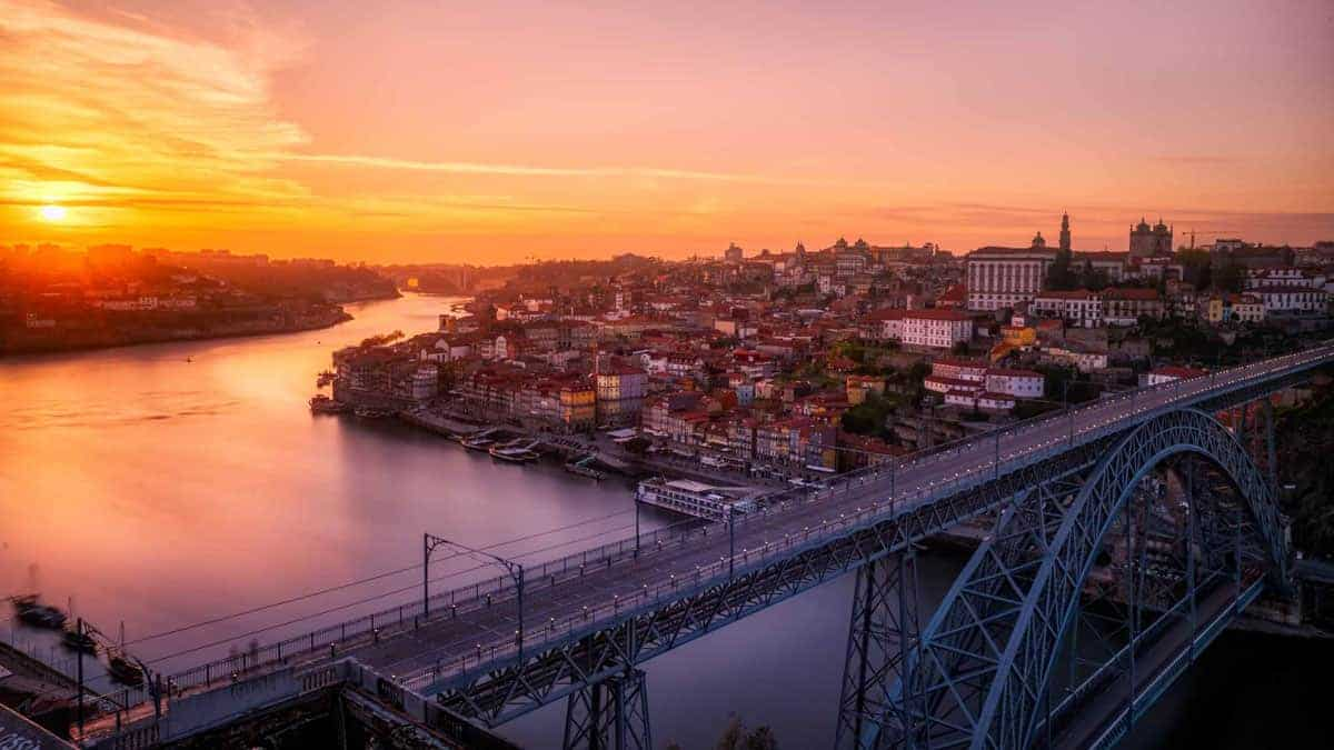 Sunrise over the Douro and Porto old town with the Dom Luis I bridge in the foreground.