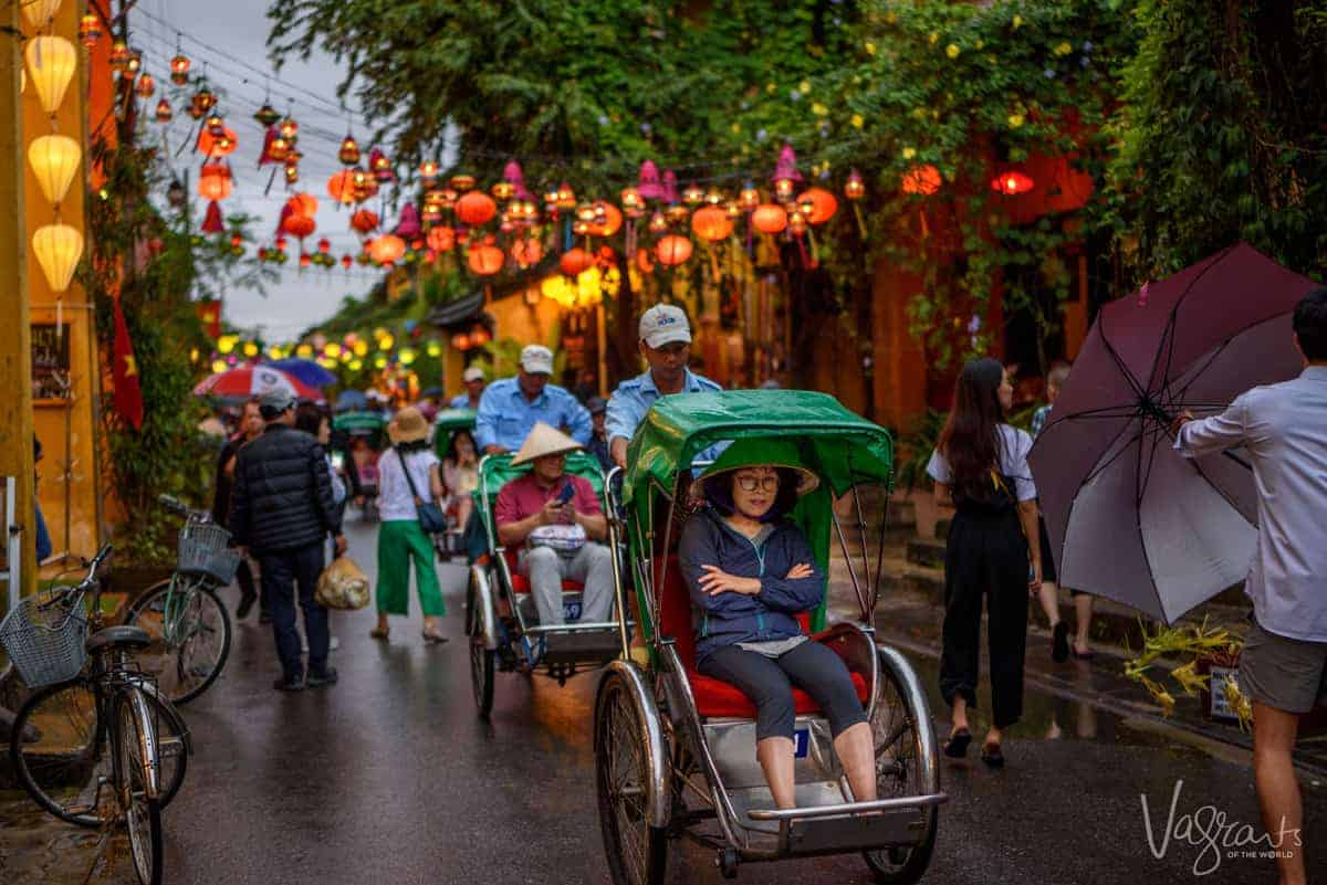 Lady taking a cyclo cab ride through the pretty streets of Old Town Hoi An