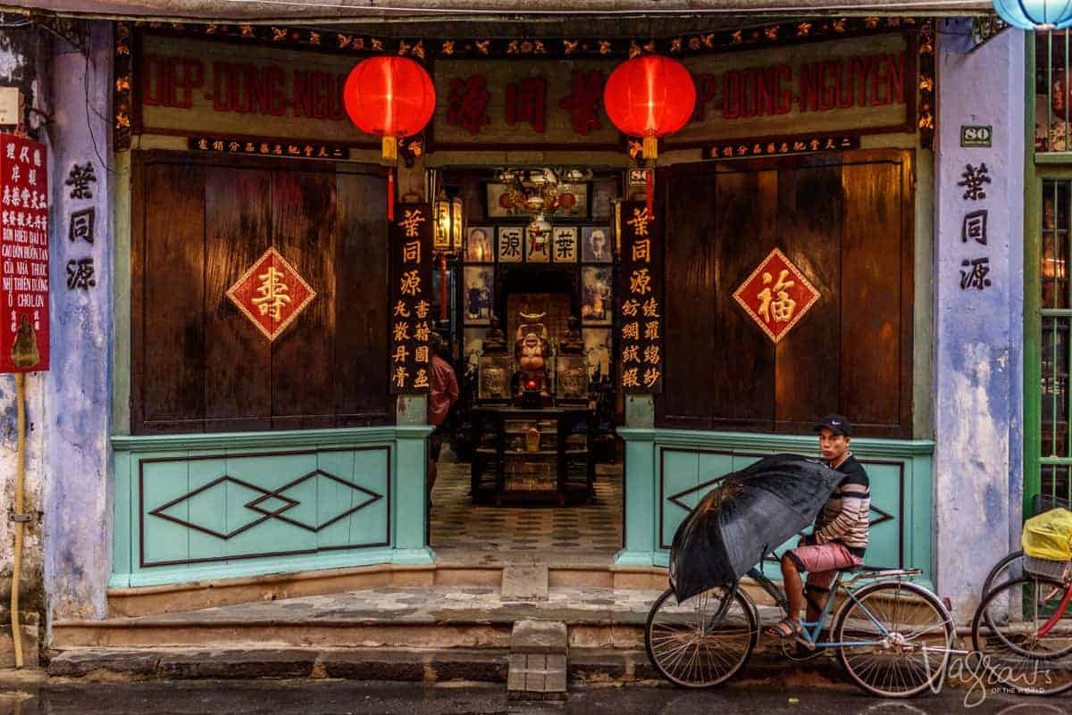 Vietnamese man on a bicycle holding an umbrella outside a heritage buddhist temple in Hoi An Old Town