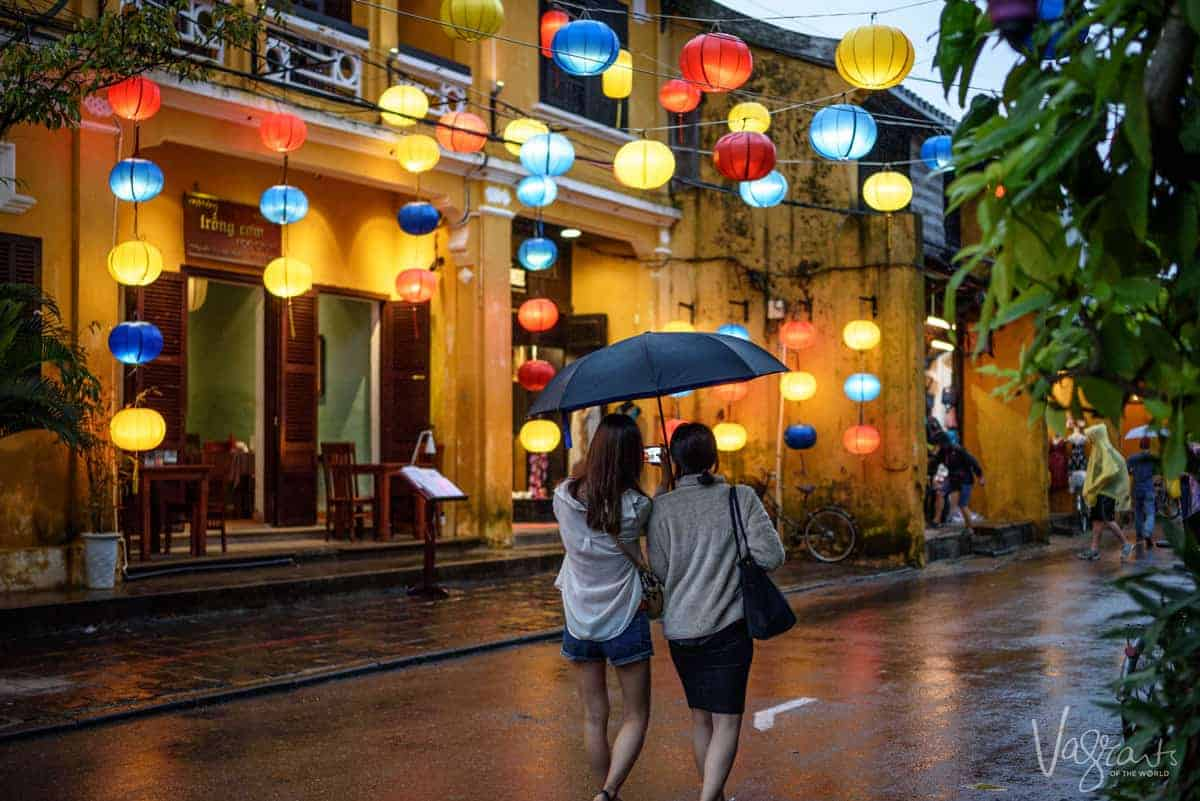 two girls under an umbrella strolling down the street shopping and looking at the lanterns at night in Old Town Hoi An.
