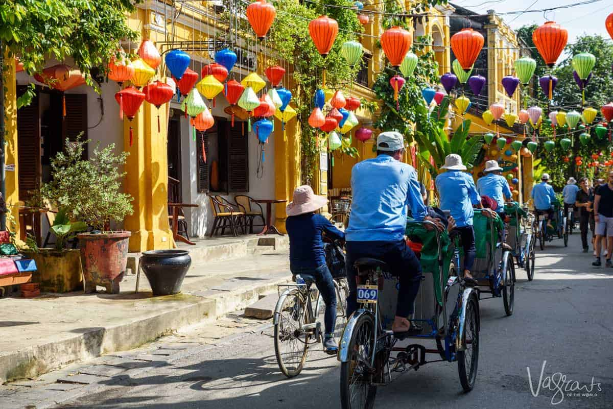 A line of cyclo drivers riding into the brightly coloured, lantern filled streets of Old Town Hoi An