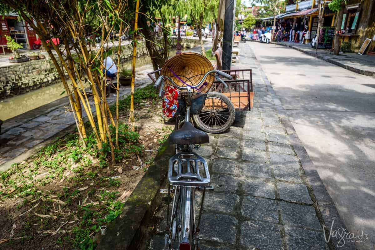 Bicycle on the side of the road in Hoi An with a traditional Vietnamese conical hat hanging from the handle bars