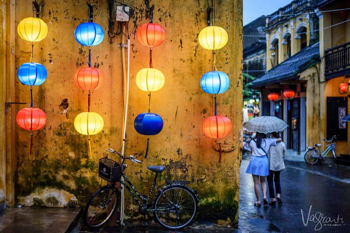 Two girls under an umbrella walking down the lantern filled streets of Hoi An Old Town at night. 2 Days in Hoi An never feels like enough.