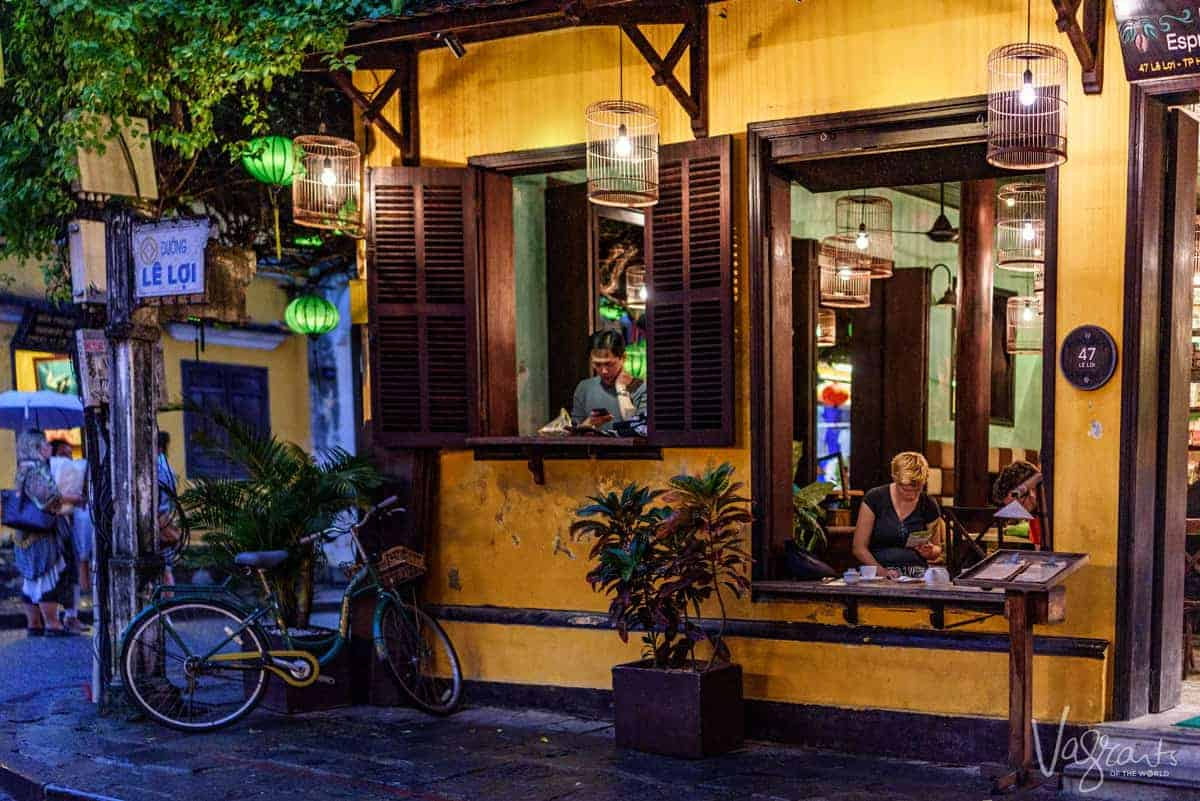 A man and lady sitting in separate windows in a pretty Hoi An cafe in Le Loi Street, Old Town