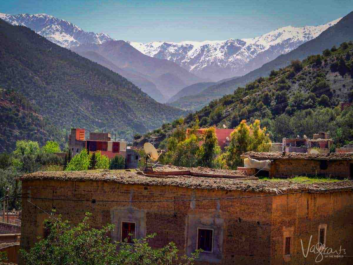 Valley in Morocco with snow capped Atlas Mountains and mud brick house.