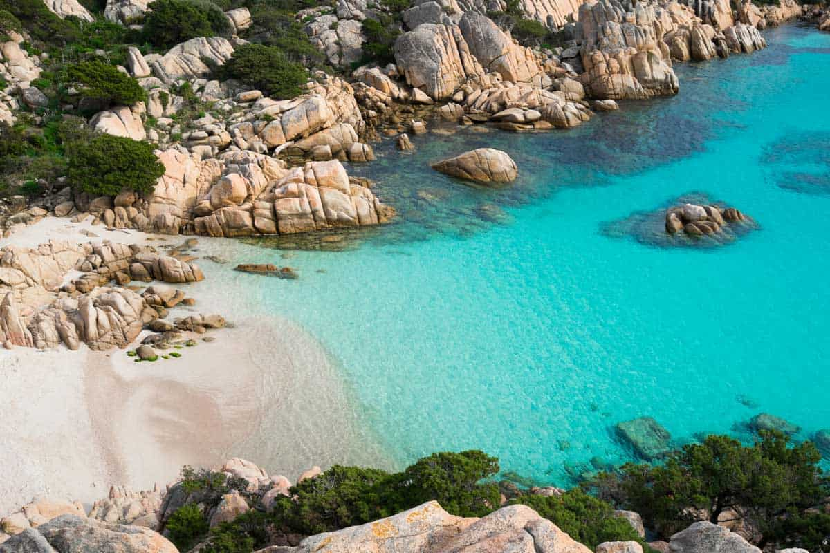 Aerial view of a white beach with clear water in a bay surrounded by rocky cliffs. This is what the best beaches in Sardinia look like