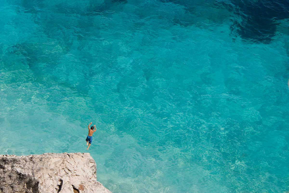 Man diving off a rock into crystal clear sea water in Sardinia