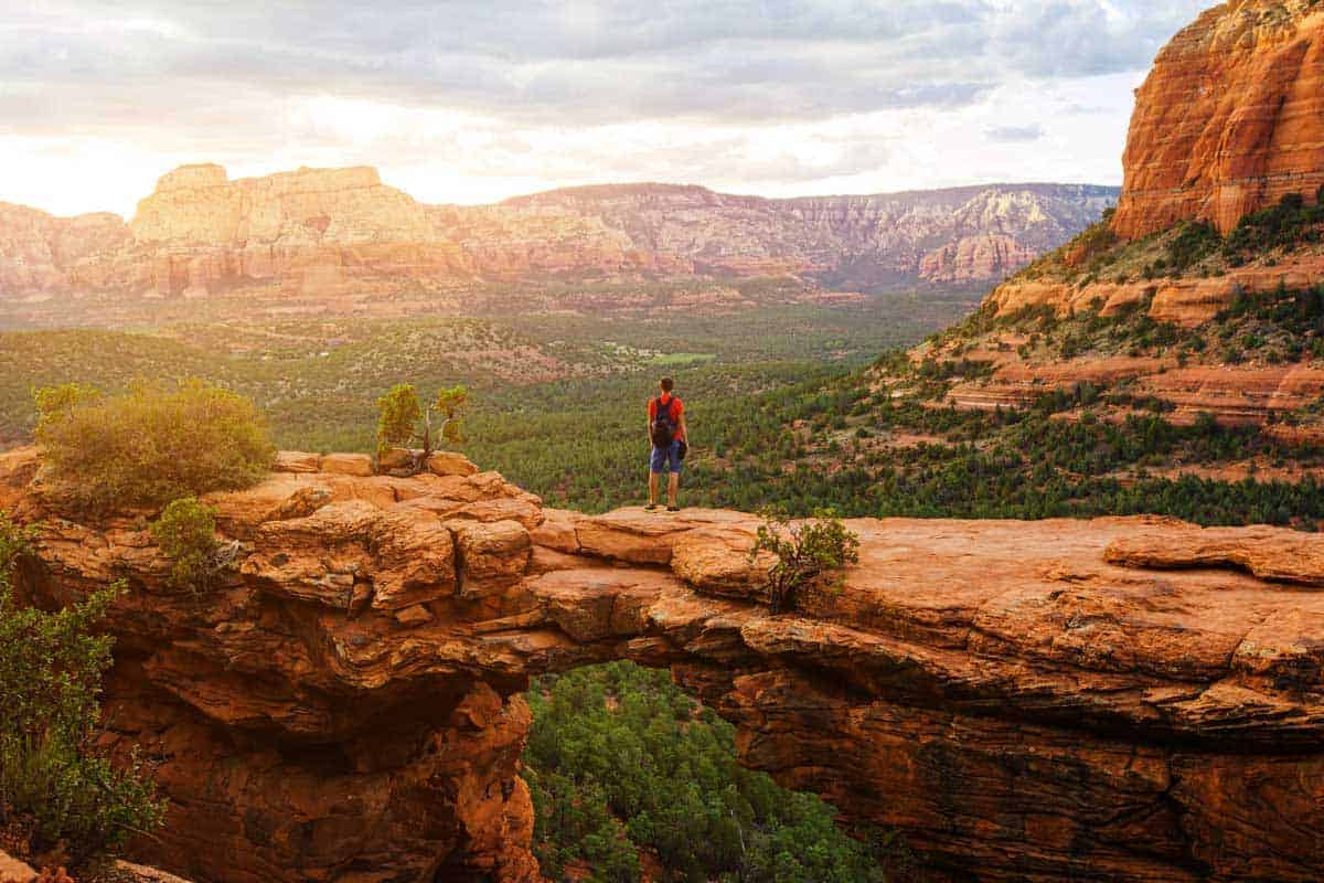 Hiking man on the natural rock bridge - Devil's Bridge in Sedona at sunset.