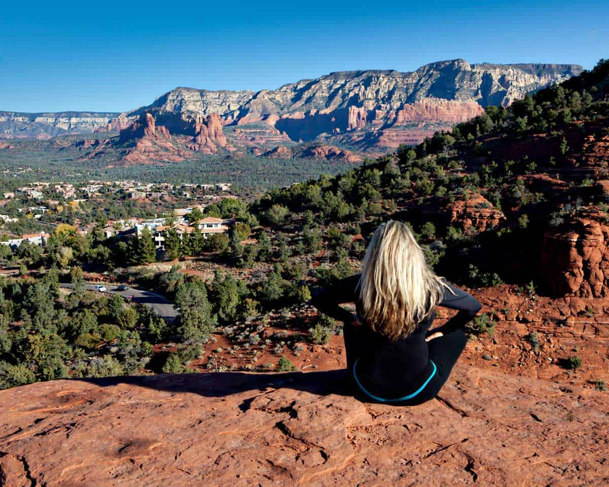 Girl sitting ona rock overlooking the town of Sedona
