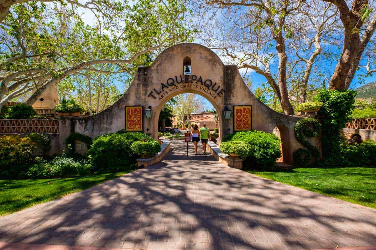 People walking through the gates into one of the most popular attractions in Sedona, Tlaquepaque Village.