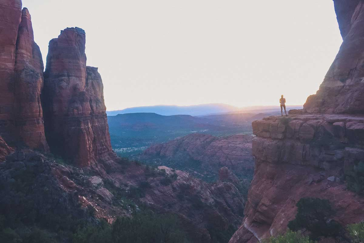 Girl standing on rocky outcrop over a large canyon at sunset.
