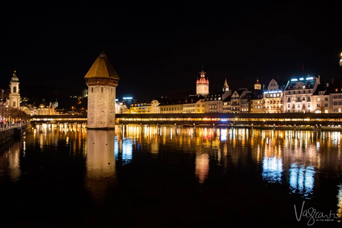 Covered wooden bridge at night with Lucerne Old Town lit up in the background