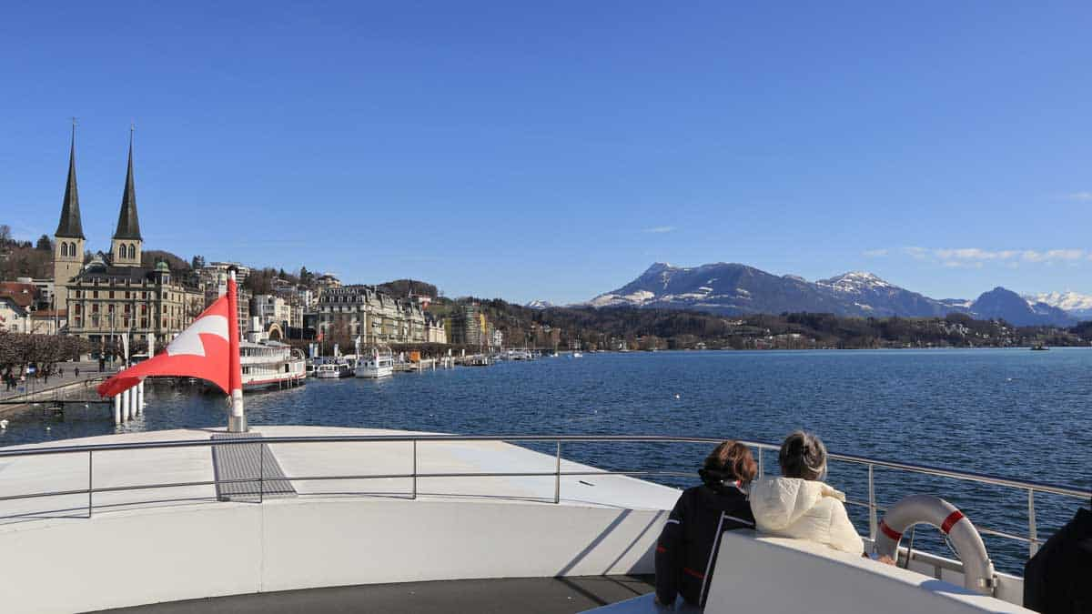Two people sitting on the foredeck of a luxury yacht on Lake Lucerne Switzerland. A cruise is one of the beat things to do in Lucerne.
