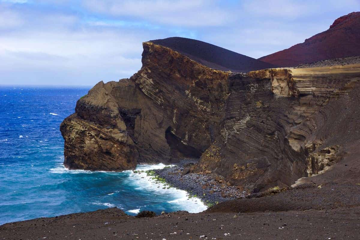 Lava beach and cliff against dark blue sea.