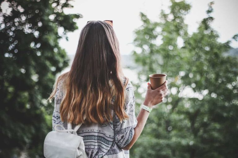 With a good travel coffee maker you can always have coffee on the go like this girl wearing the backpack enjoying the view with a cup of coffee.