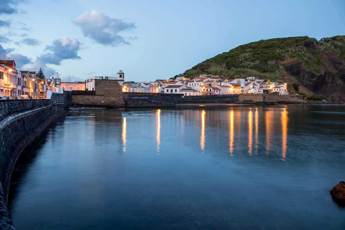 Lit houses and reflections on waterfront in the evening on Faial island.