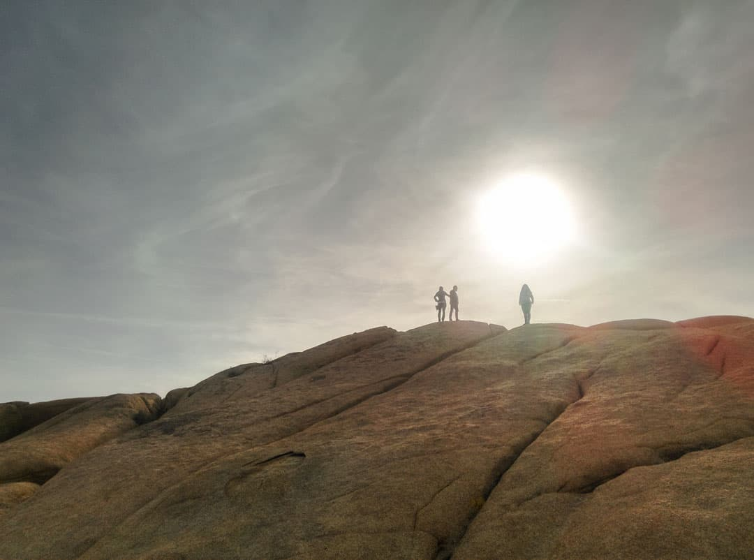 people standing on top of a large boulder looking into the sun in Joshua Tree NP