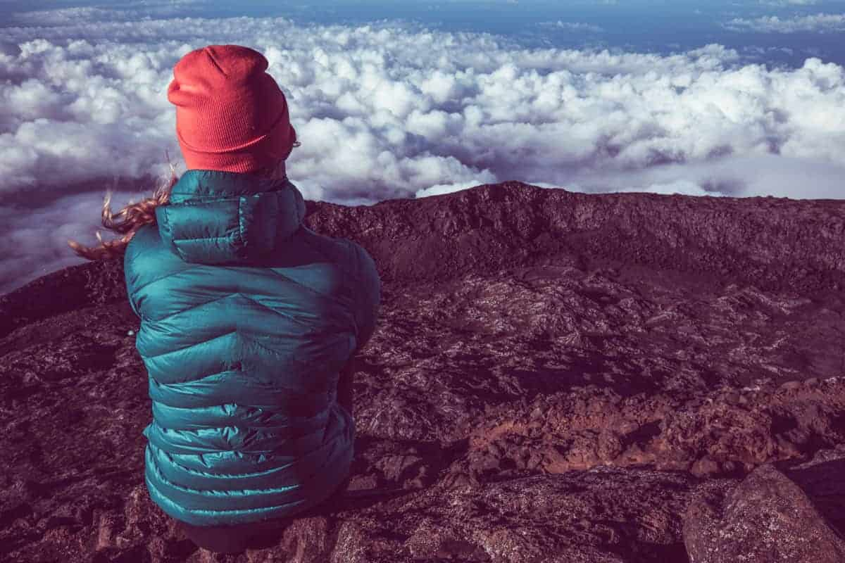Hiker resting amongst the clouds on volcanic rim on Pico island.