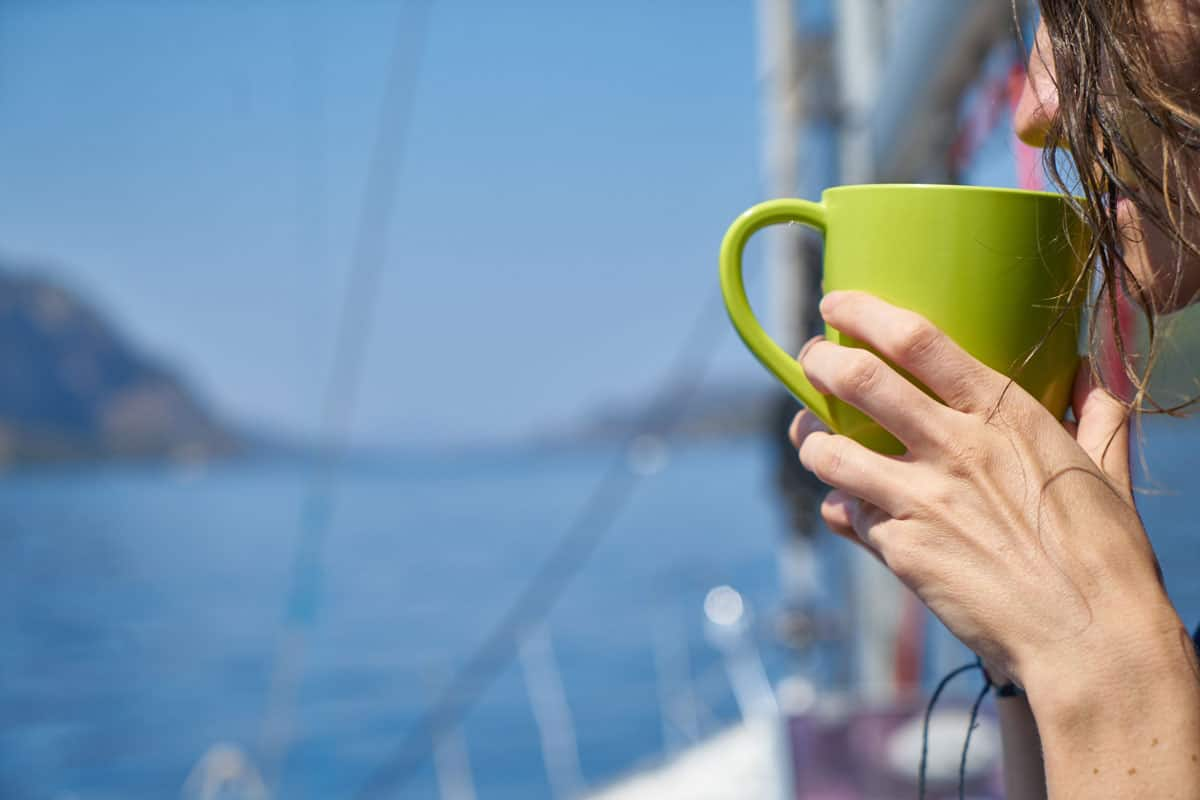 girl enjoying a cup of coffee next to the sea.