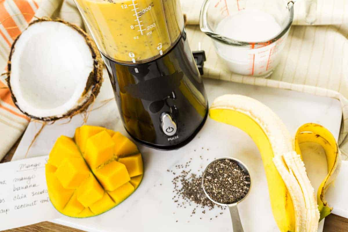 Looking down on a table with mango,banana, and chia seeds cut up for the portable blender.