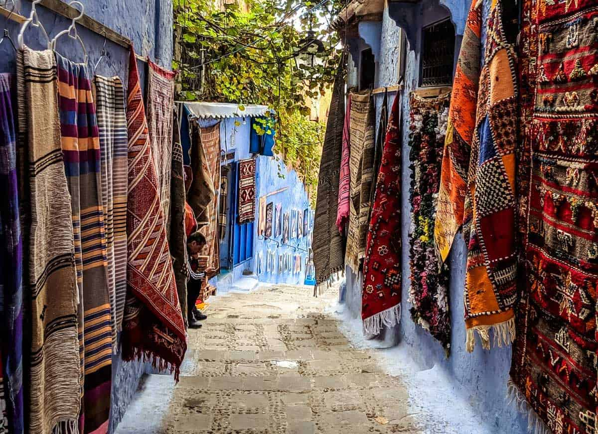 Chefchaouen alley lined with colourful rugs and mats.