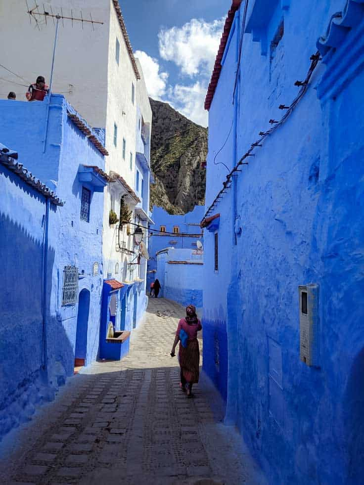 Tourist walking down blue walled alley in Chefchaouen.