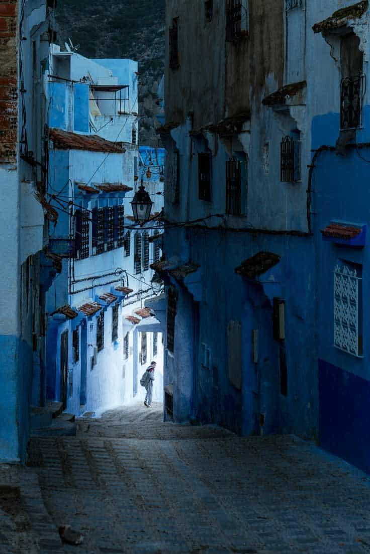 Dark blue, man in alley in Chefchaouen at night.