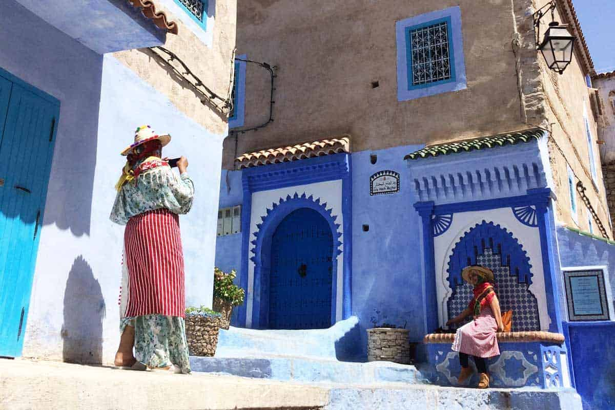 Moroccan girls in traditional dress outside blue house in Chefchaouen.