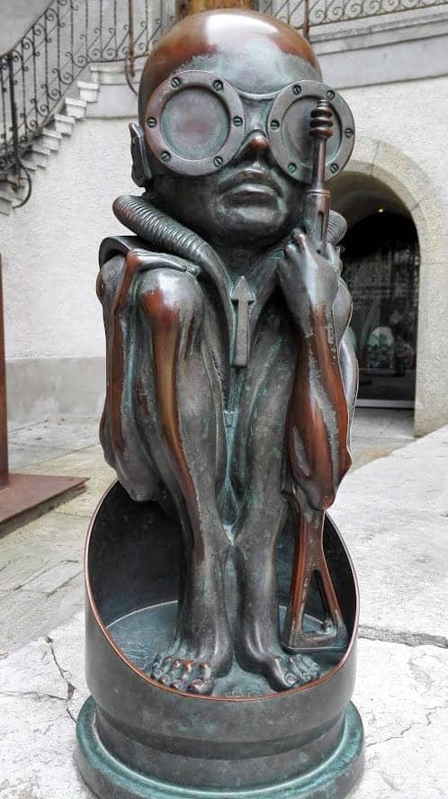 Bronze statue of an alien outside the H R GIGER MUSEUM in Gruyere.