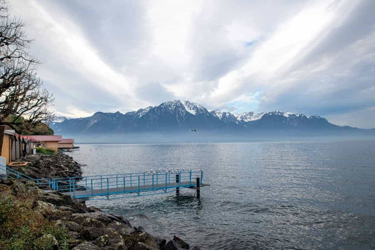 Jetty out into the lake and clouds over the mountains and lake, Montreux