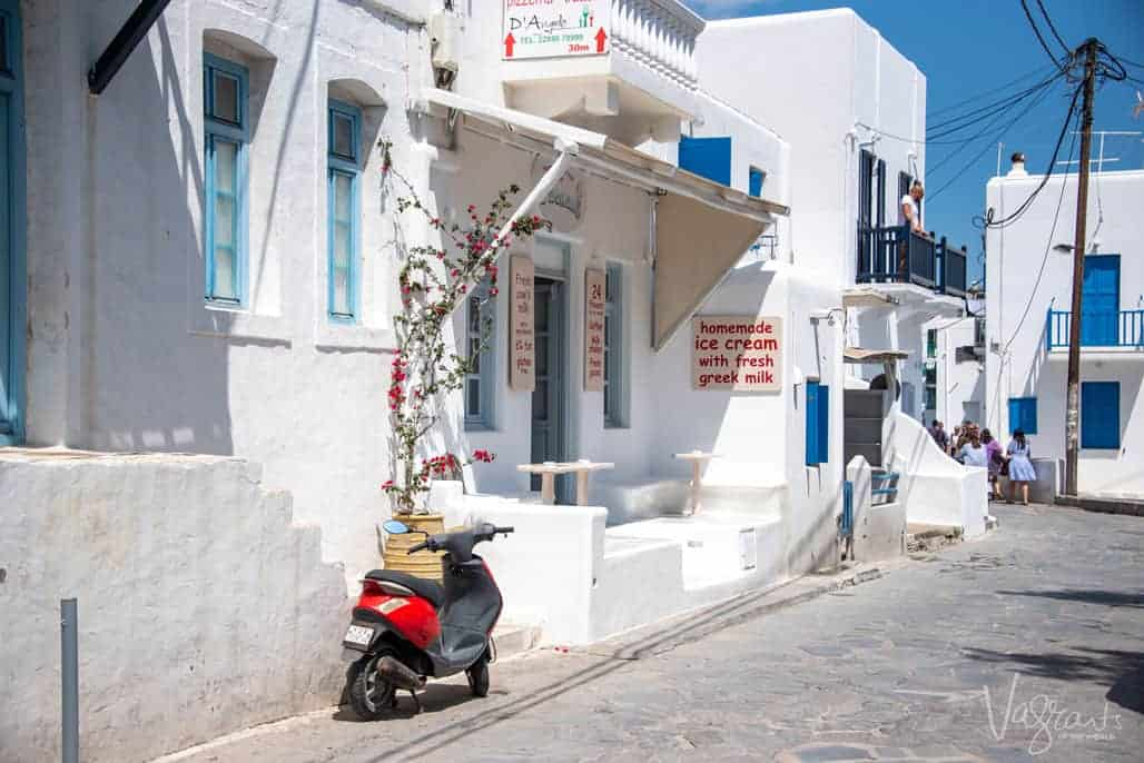 Scooter parked outside whitewashed shops selling ice cream made with greek milk.