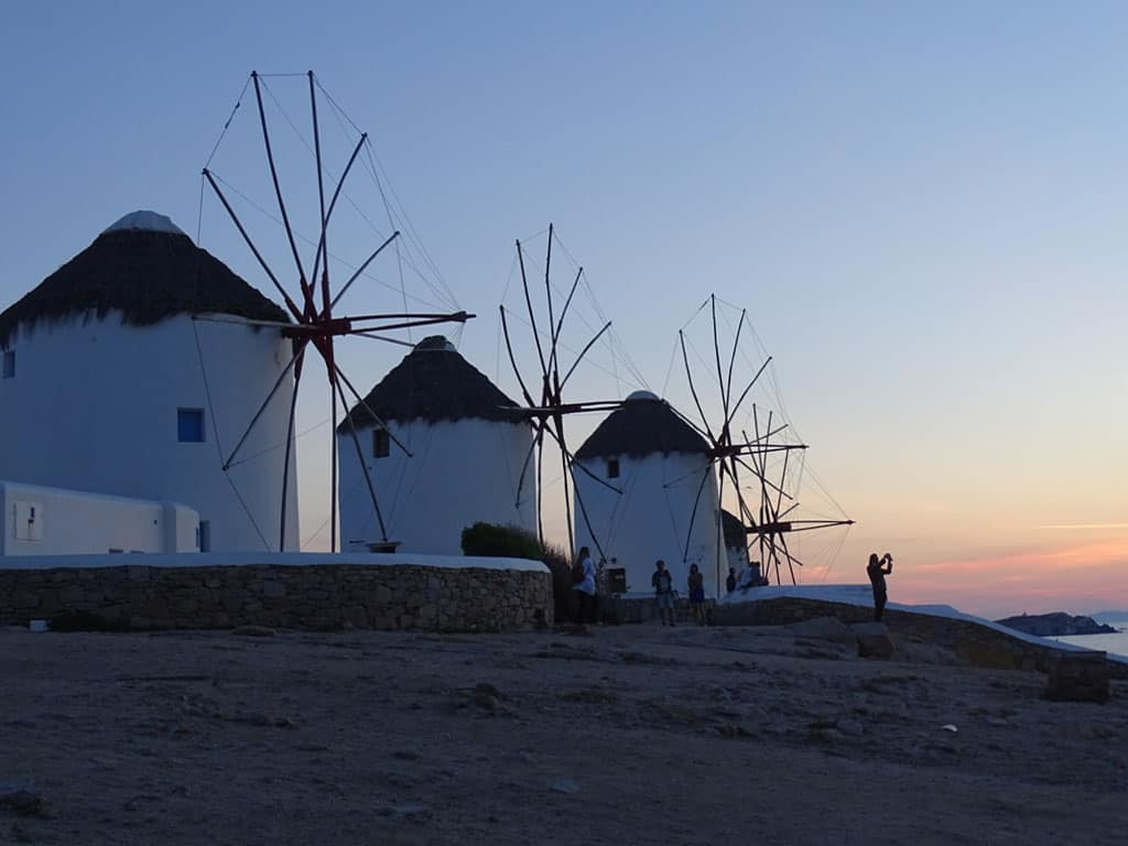 Photographers at Mykonos windmills enjoying sunset.