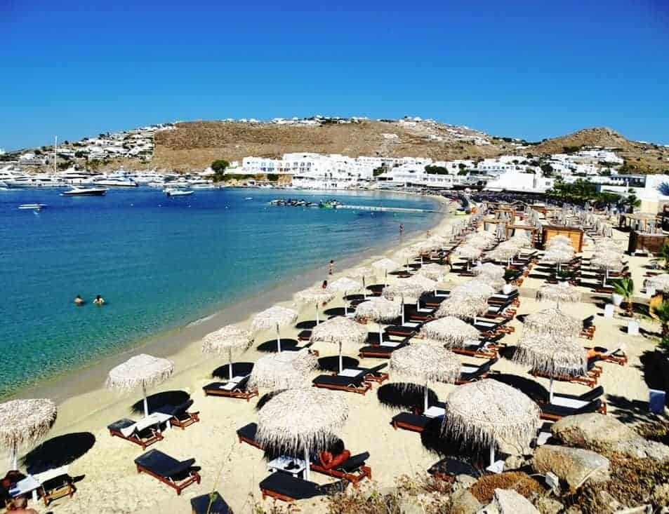 Ornos beach covered in beds and parasols inviting tourists to Mykonos for the summer.