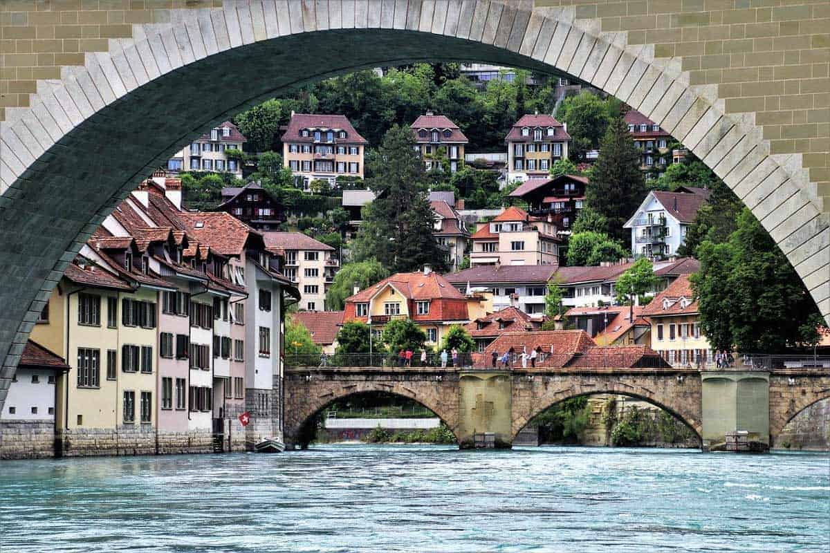 Arched stone bridges and terrace houses lining the river in old town, Bern