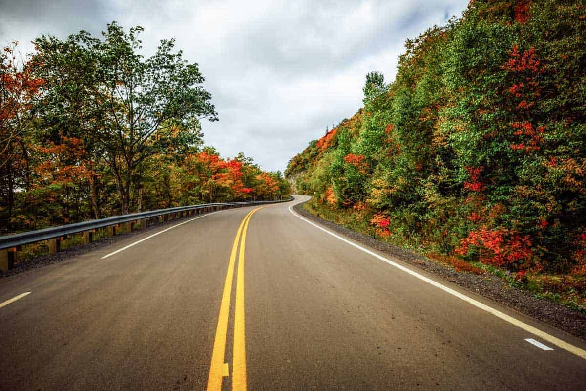 Fall foliage lines the highway on a road trip to Cabot Trail, Nova Scotia