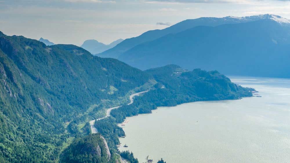 Canada road trip leads you along a winding road next to the lake below Squamish.