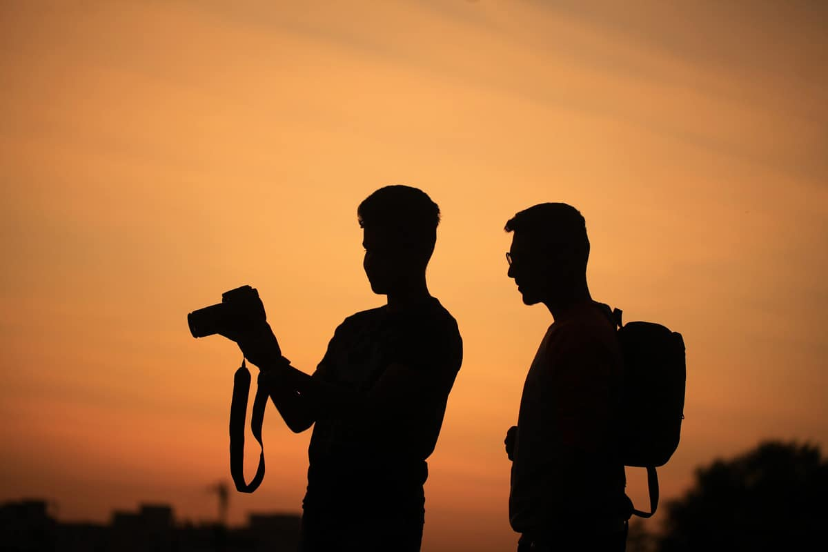 Silhouette of a traveller holding a camera as his friend looks on learning travel photography