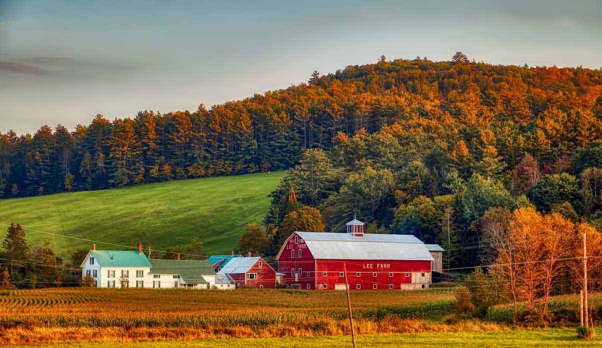 Big red Barn house surrounded by green fields and fall forest, New Hampshire.