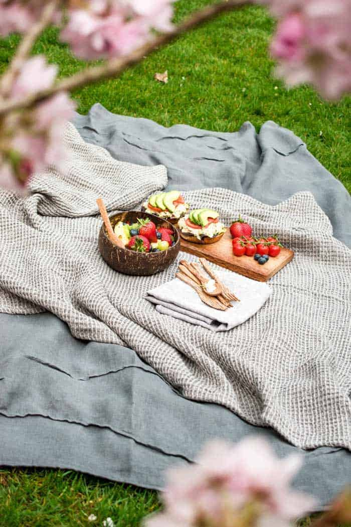 Picnic setting on a blanket with wooden forks and a platter of vine tomatoes, avacado and salad on an open roll with a bowl of fruit salad.