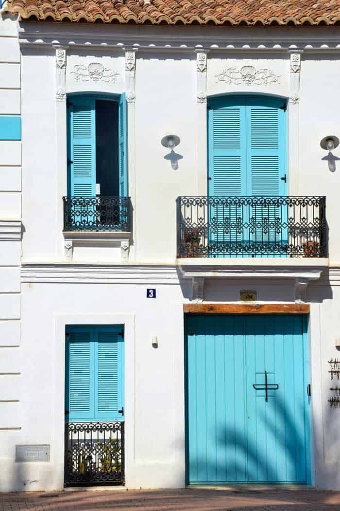 Sky blue shutters and doors behind iron railings of a white house in Valencia.