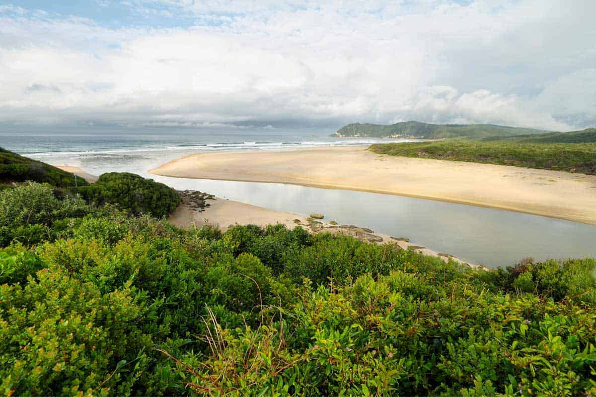 A river between two sandy beaches emptying into the sea at Sedgefield.