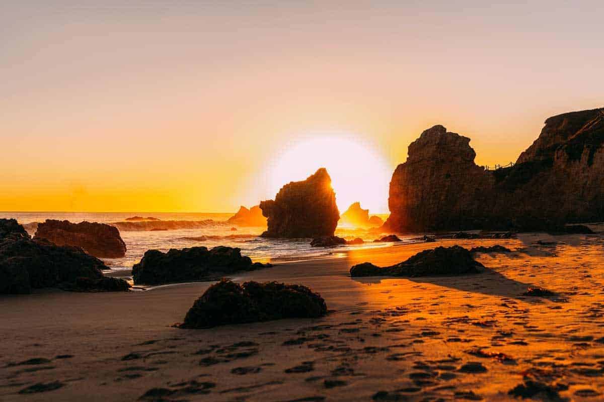 The perfect ball of the sun setting behind the rocks on a Malibu beach.