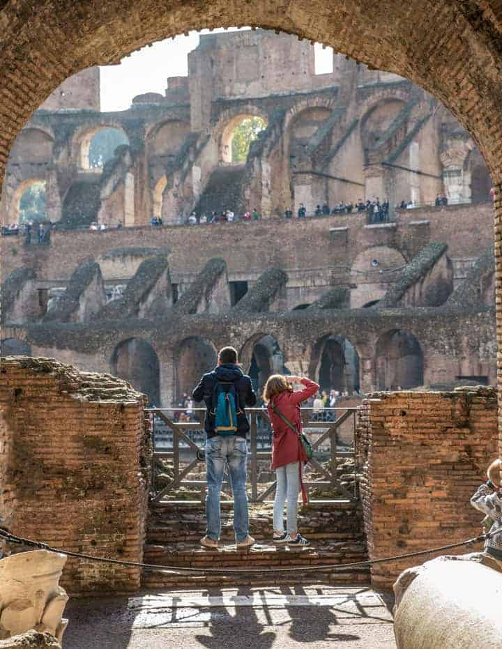 Young man and girl from behind taking photos in the Colosseum in Rome.