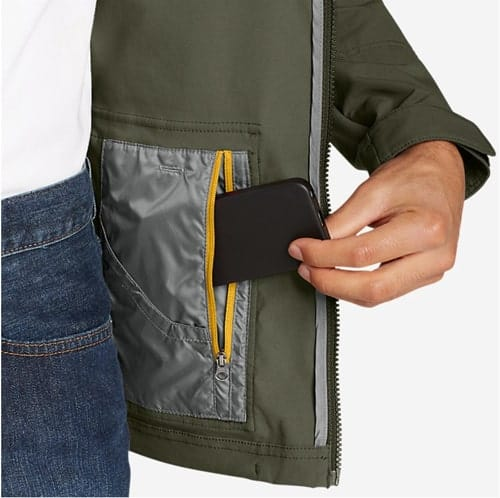 Close up of a man inserting a phone into an interior hidden pocket in his jacket.
