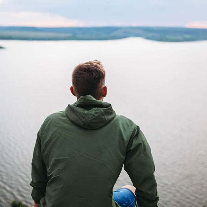 Young man sitting on a rock ledge looking out to sea wearing a hooded travel jacket.