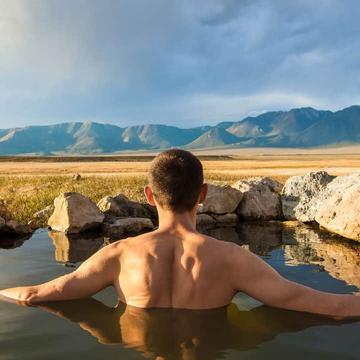 Young man soaking in a natural hot spring in a feild with mountains in the distance.