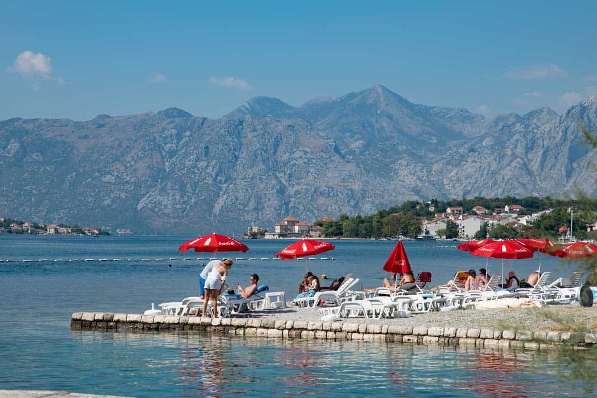 People on sunlounges with red umbrellas on the shore of Bay of Kotor Montenegro.