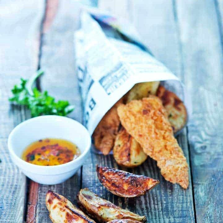 Fish and chips on a table wrapped in a paper cone.