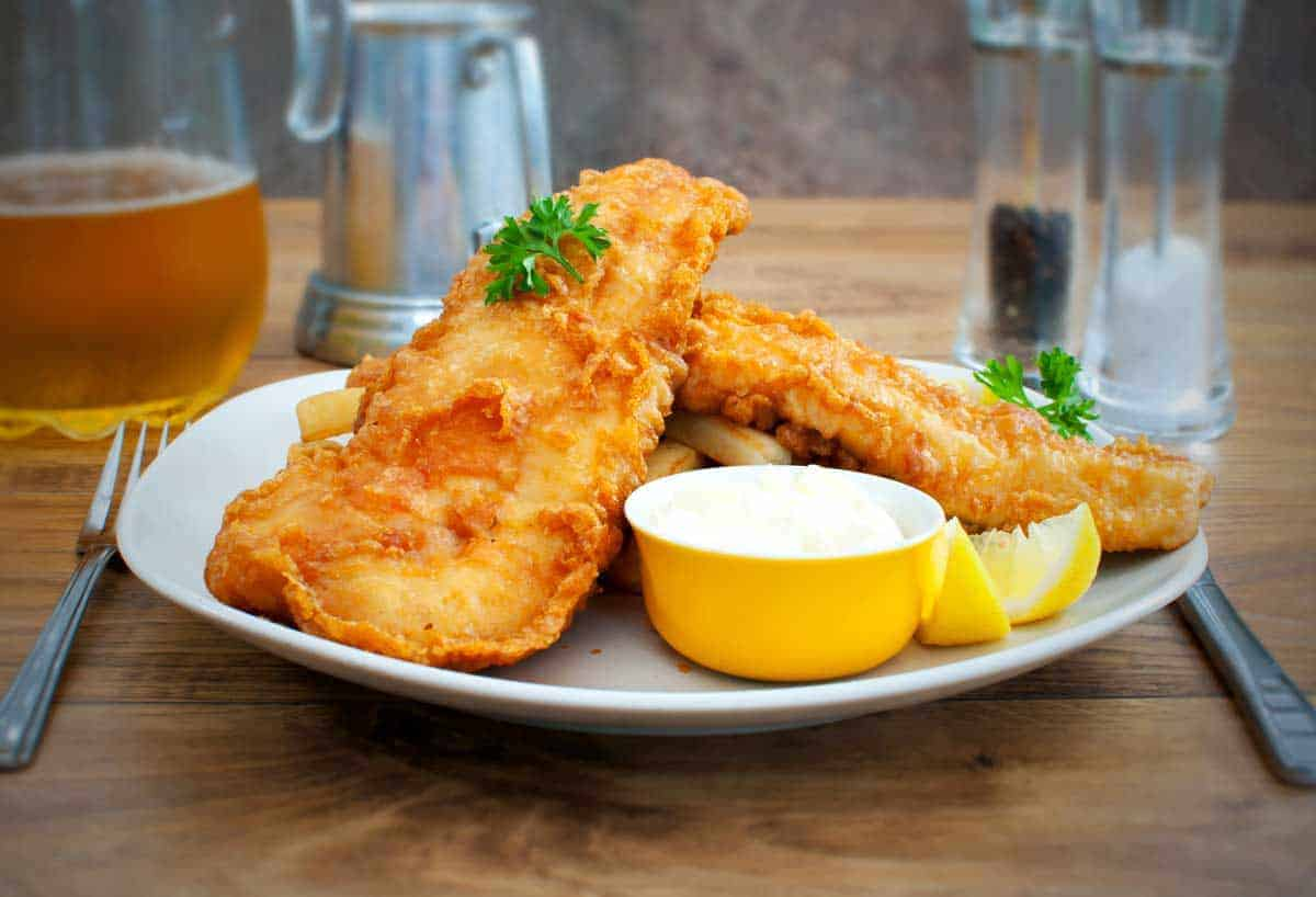 Fish and chips on a plate with tartare sauce.